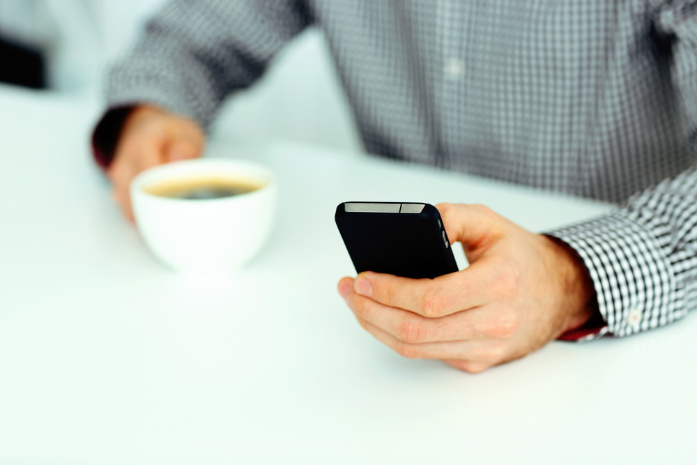 Closeup image of a male hand typing on smartphone and holding cup of coffee