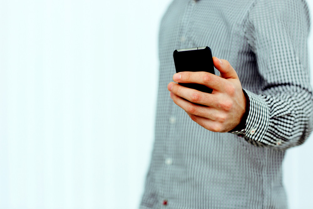 Closeup image of a male hand holding smartphone isolated on a white background