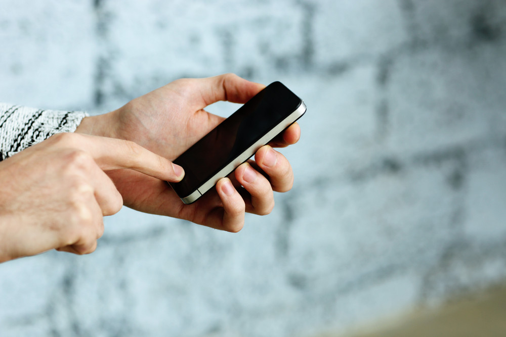 Closeup image of a male hand holding smartphone