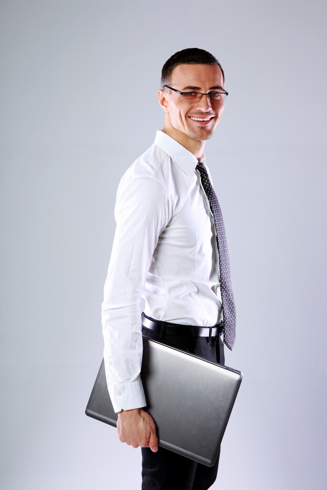 Cheerful businessman standing with laptop over gray background