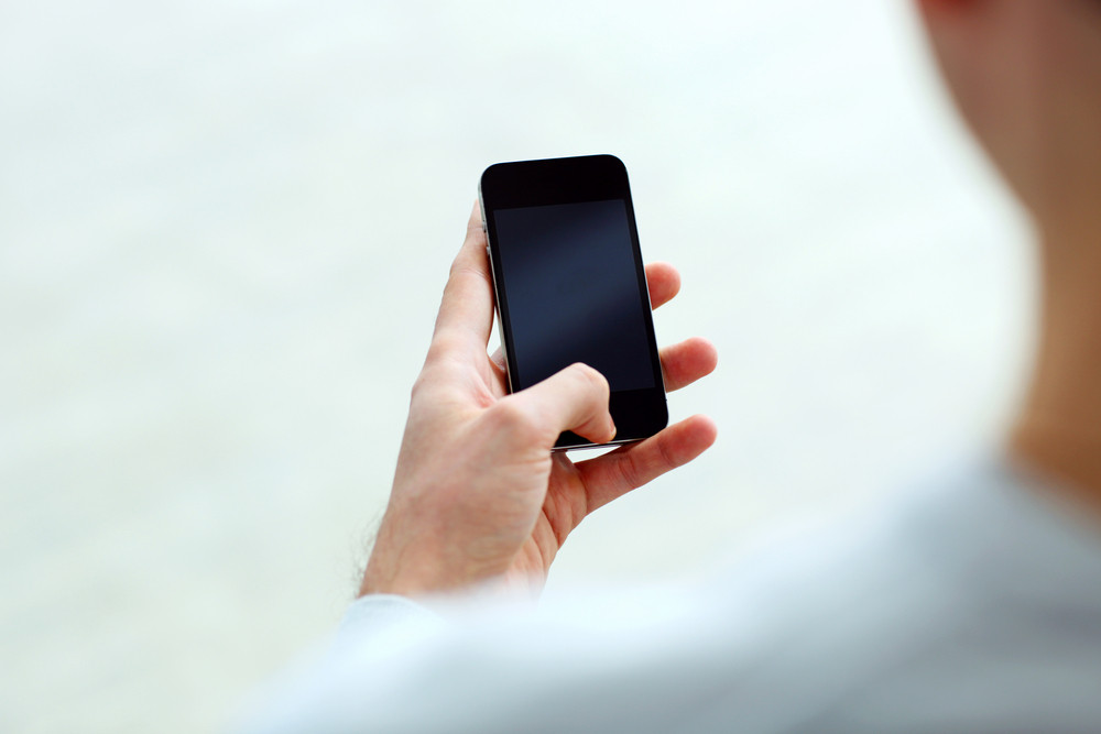 Closeup image of a man holding smartphone and looking at display isolated on a white background