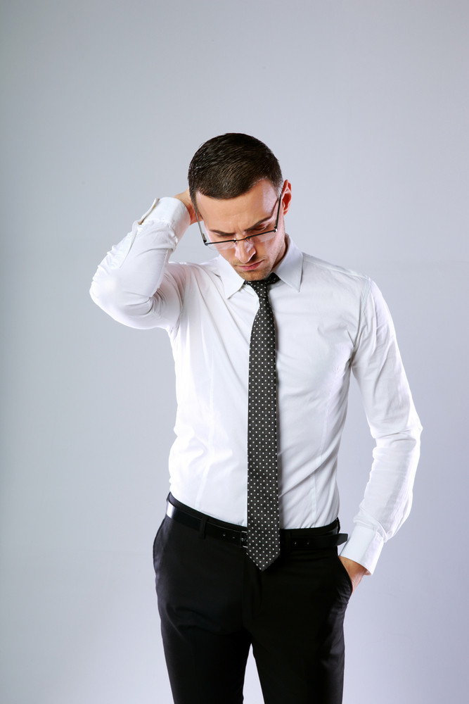 Portrait of a pensive businessman in glasses on gray background