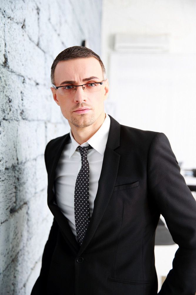Handsome businessman standing near brick wall