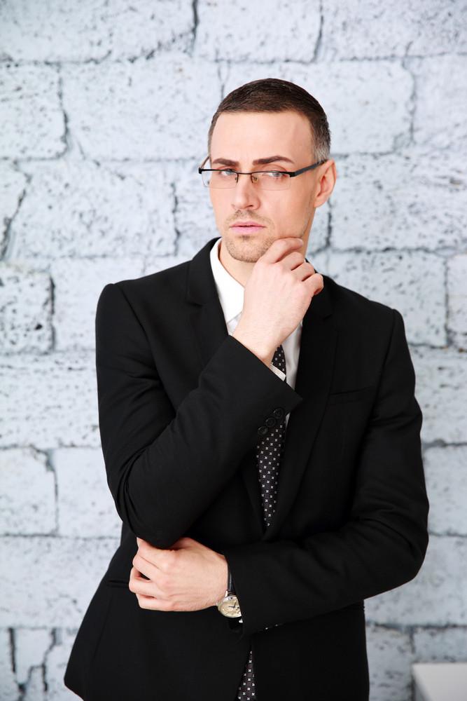 Confident businessman standing near brick wall