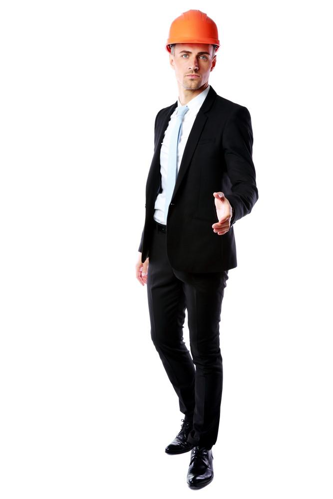 Full length portrait of a businessman in helmet offering handshake over white background