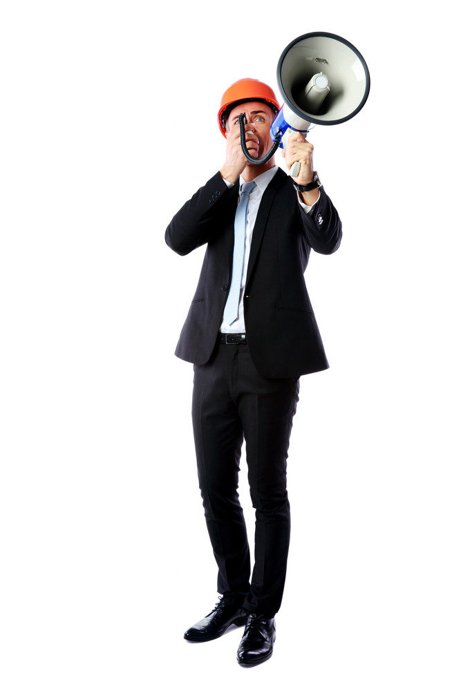 Full-length portrait of a businessman shouting with megaphone over white background