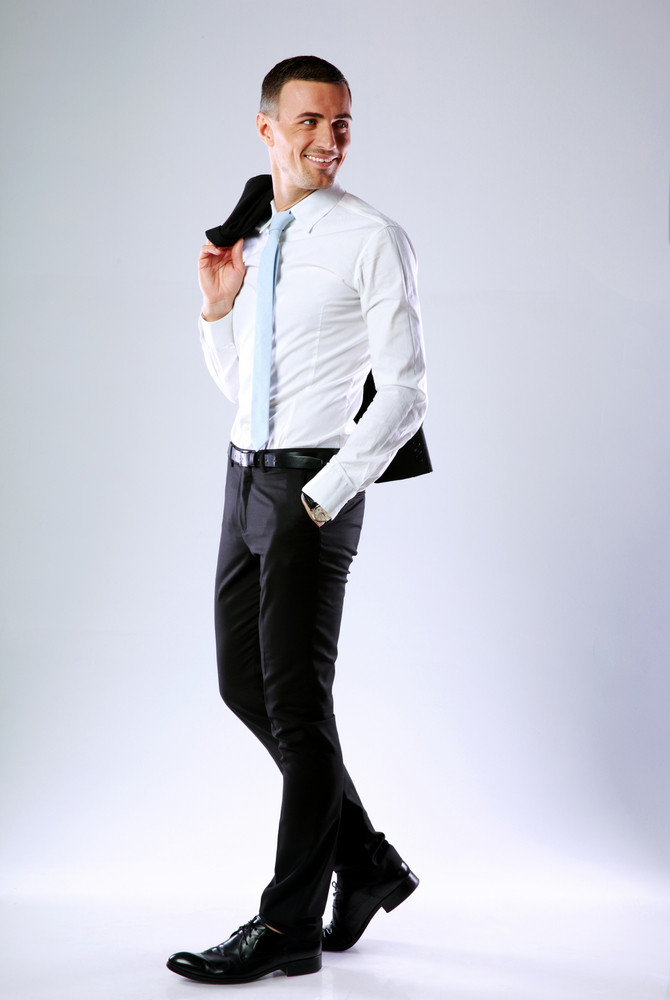 Full length portrait of a happy business man holding jacket on shoulder on gray background