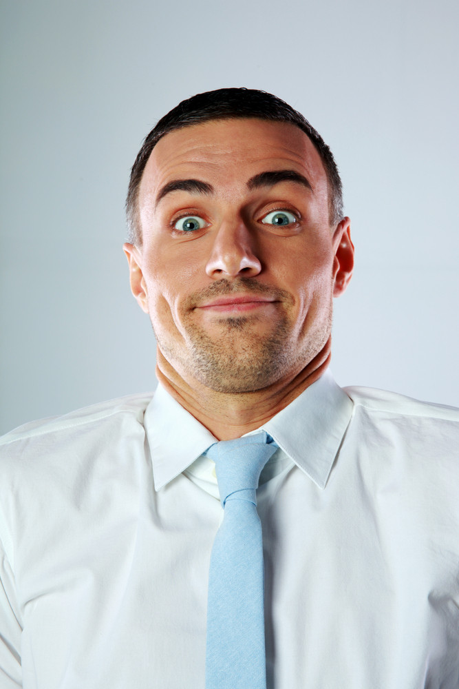 Businessman with a surprised expression on gray background
