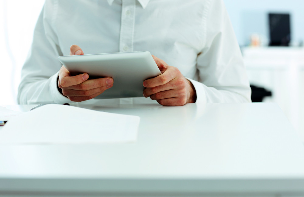 Businessman holding a tablet computer and sitting at the table in office