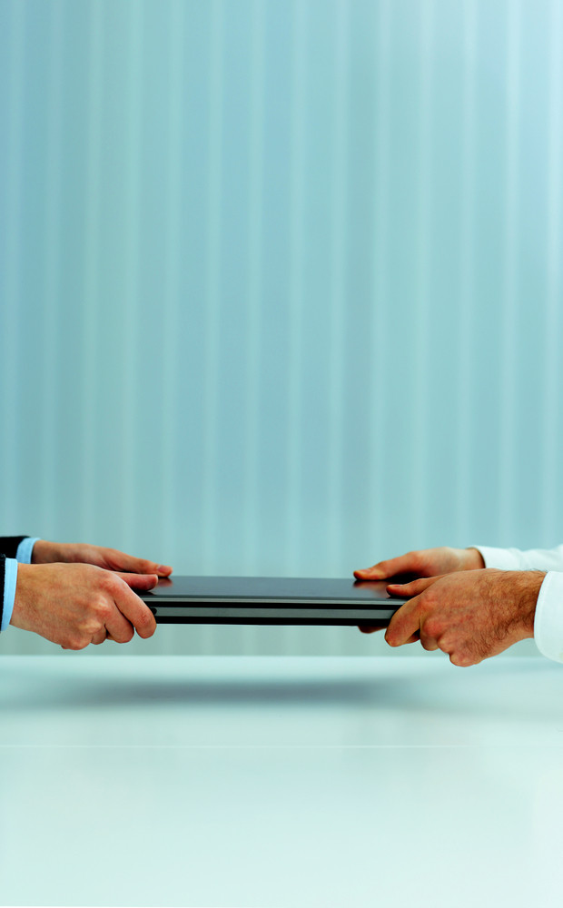 Closeup image of a business hands pulling a laptop. Competition for new vacation.