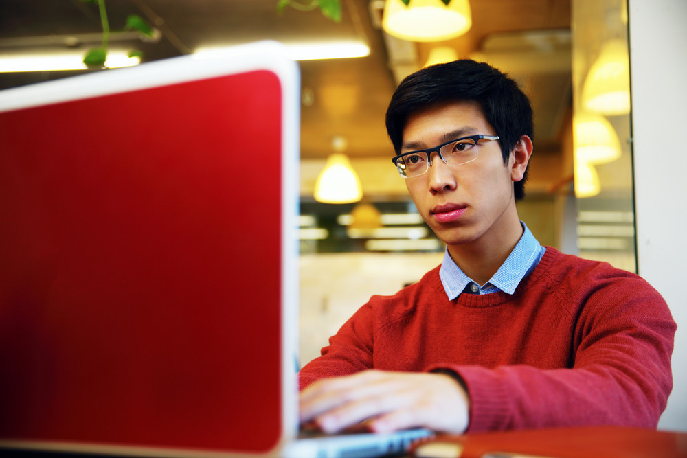Smart asian man in glasses working on laptop in office