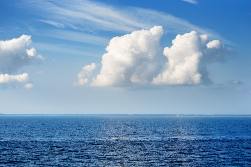 Idillic Landscape Of Blue Sea And Big Ornamental Clouds