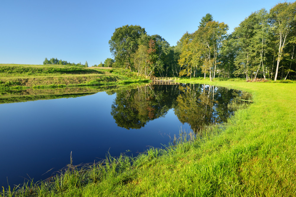 Calm Countryside Lake With A Small Bridge