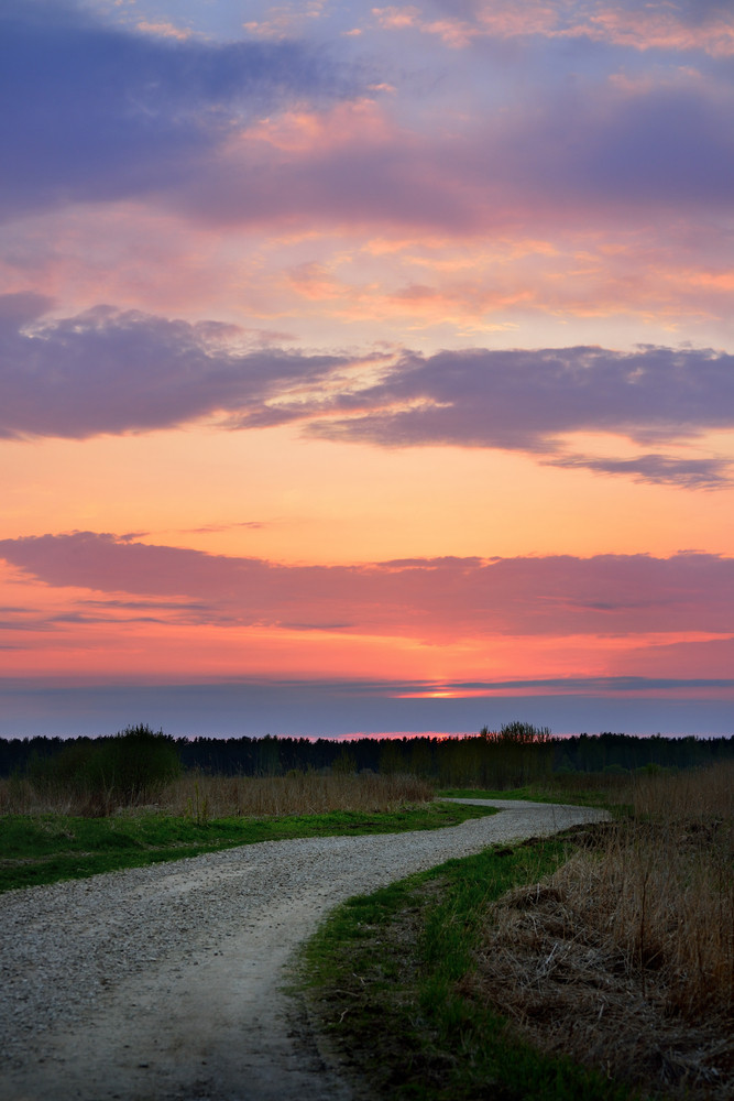 Classic Countryside Landscape With Road Against Dramatic Sunset