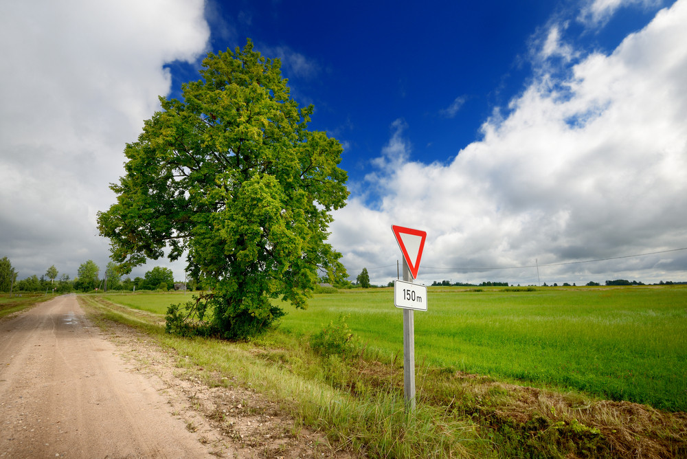 Green Field And The Road Sign On A Country Road Against Stormy Sky
