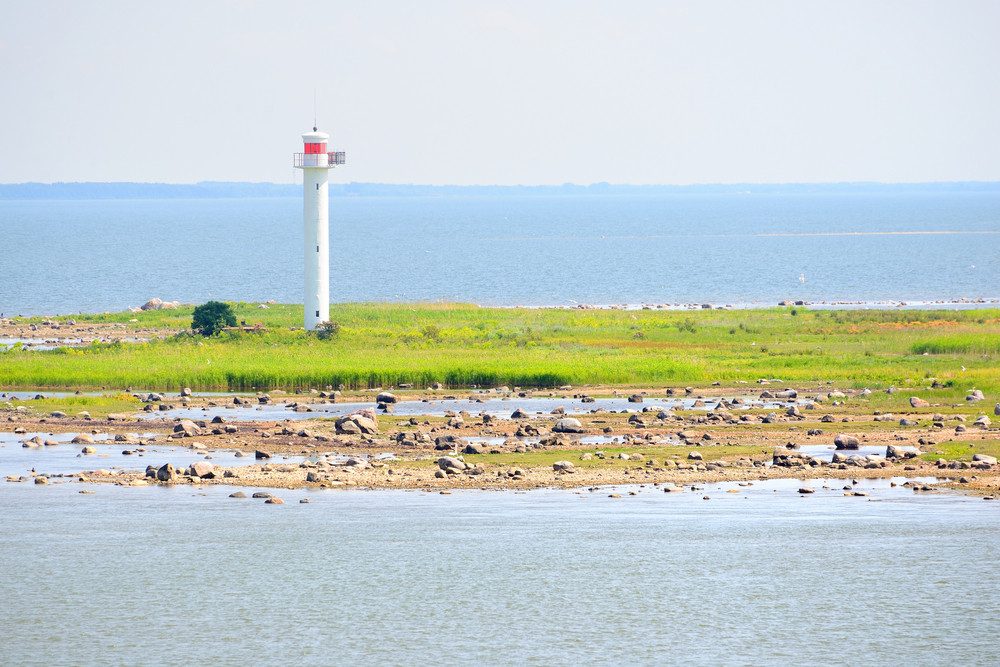White Lighthouse On The Rocky Island In Blue Sea