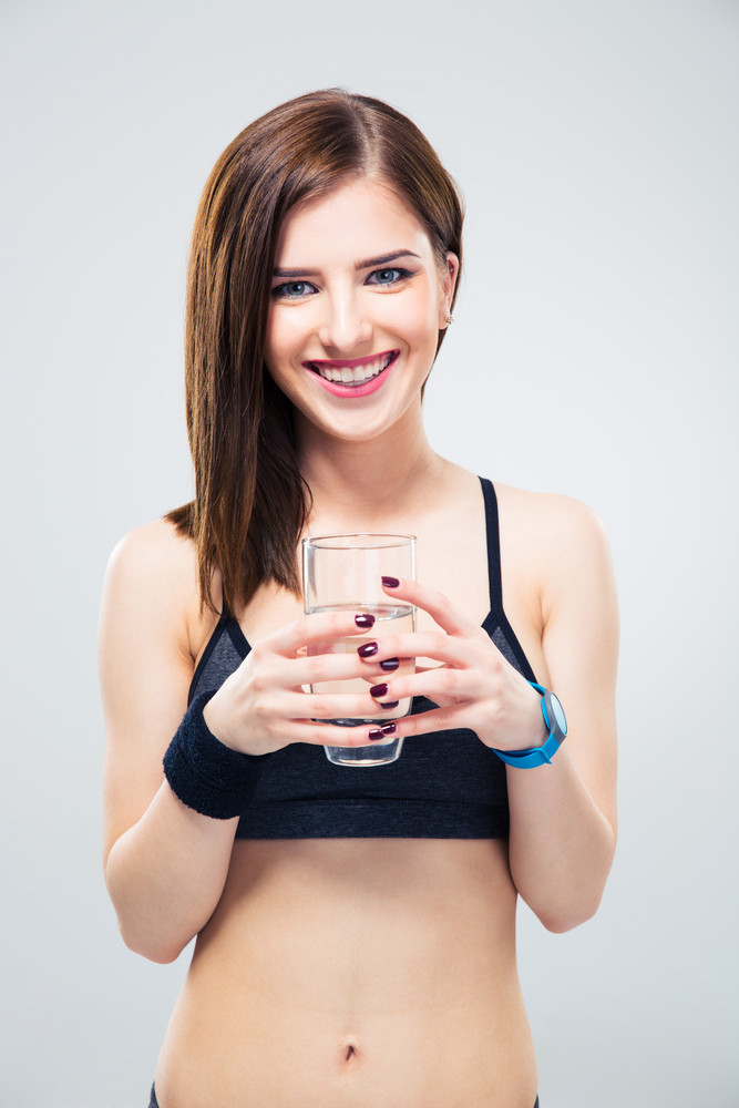 Smiling sporty woman holding glass of water