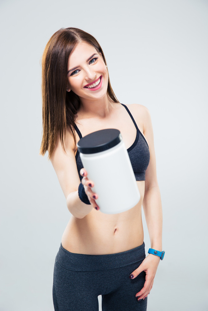 Happy sporty woman giving jar of protein on camera