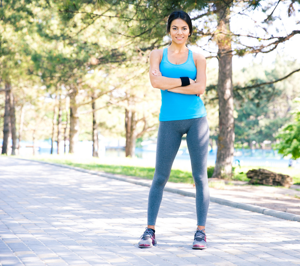 Fitness pretty woman standing with arms folded outdoors