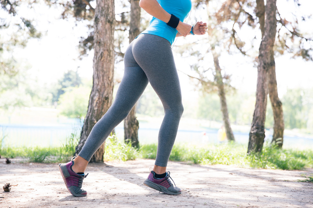 Fitness woman running outdoors in park