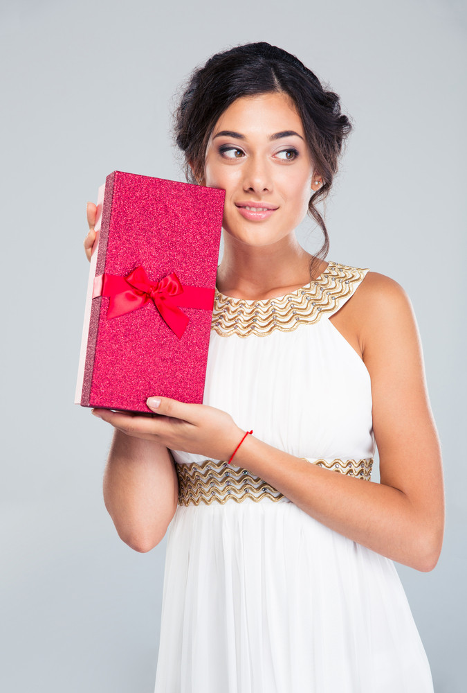 Happy woman in white dress holding gift box