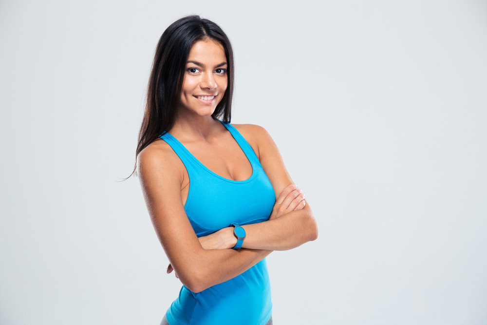 Happy fitness woman standing with arms folded