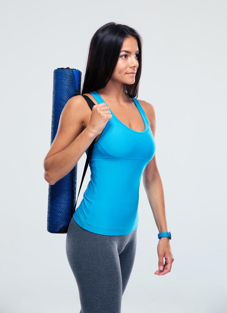 Fitness woman holding yoga mat
