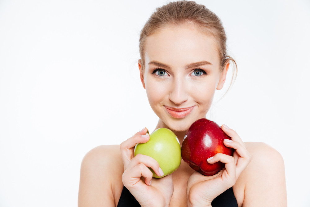 Closeup of smiling pretty sportswoman with green and red apples
