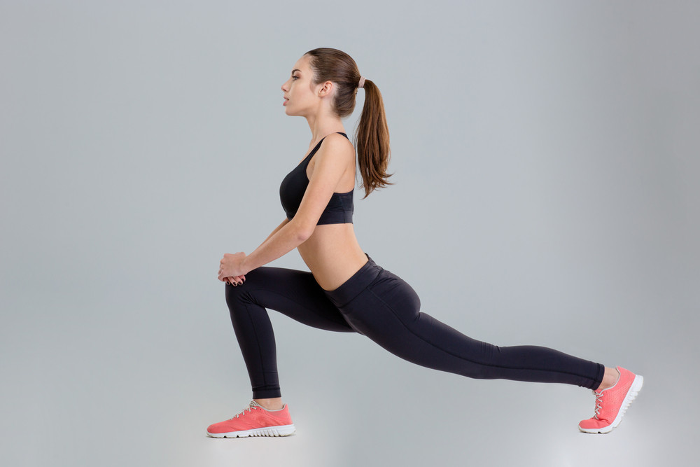 Beautiful concentrated fitness girl doing stretching exercise