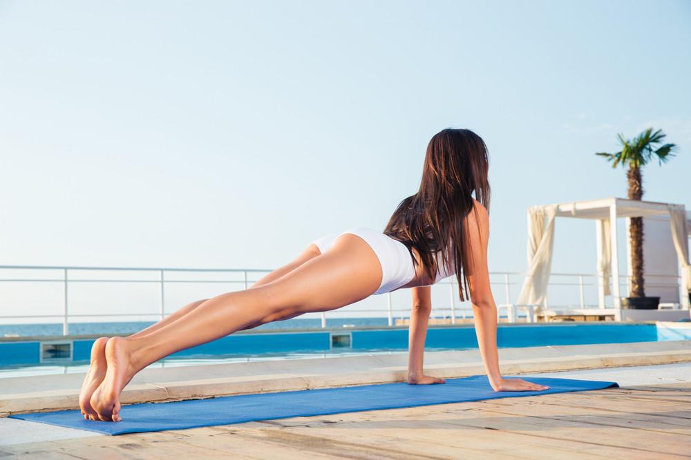 Girl making yoga exercises on yoga mat