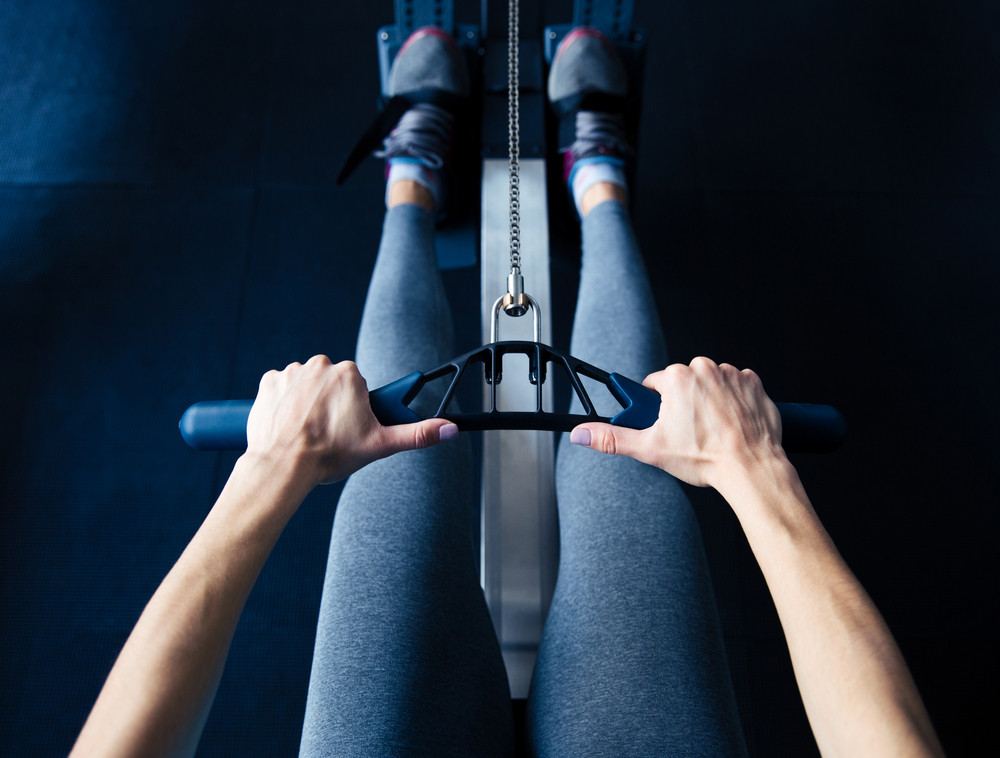 Closeup image of a woman working out on simulator at gym