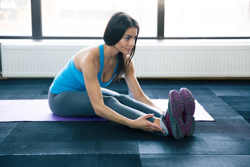 Young woman doing yoga exercises on yoga mat