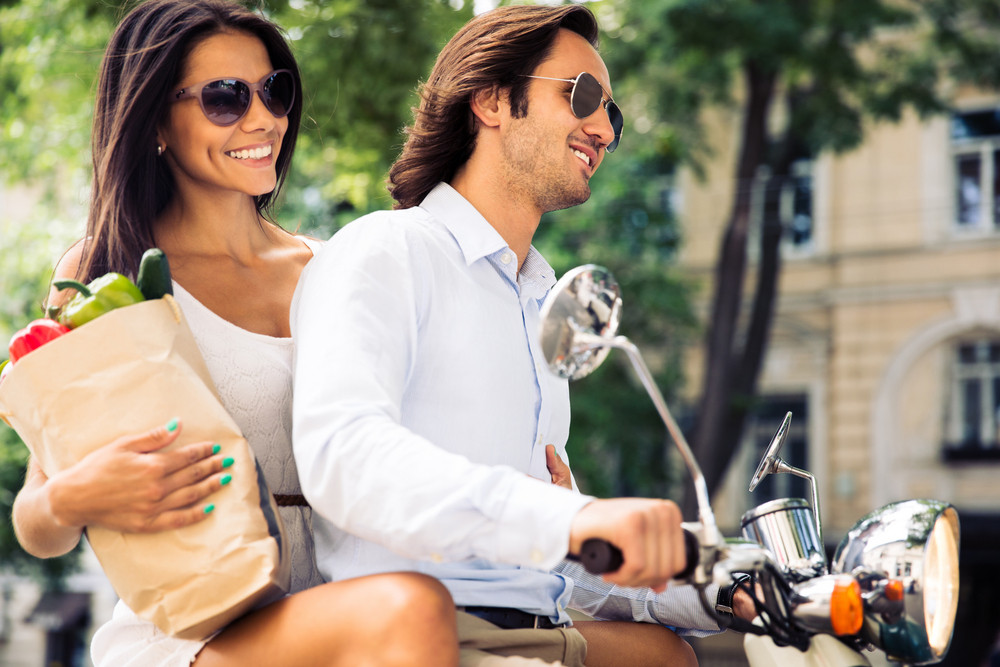 Smiling young couple riding a scooter