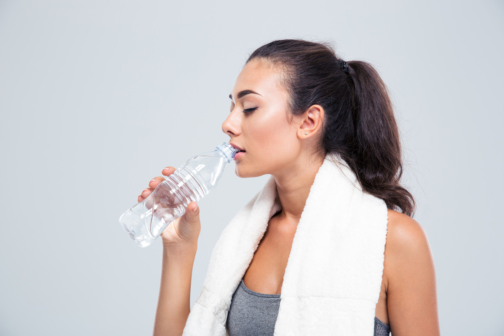 Fitness woman with towel drinking water