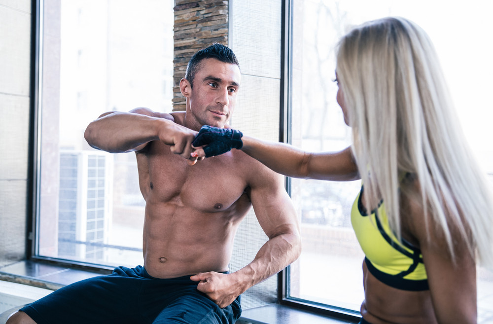 Muscular man with woman at gym