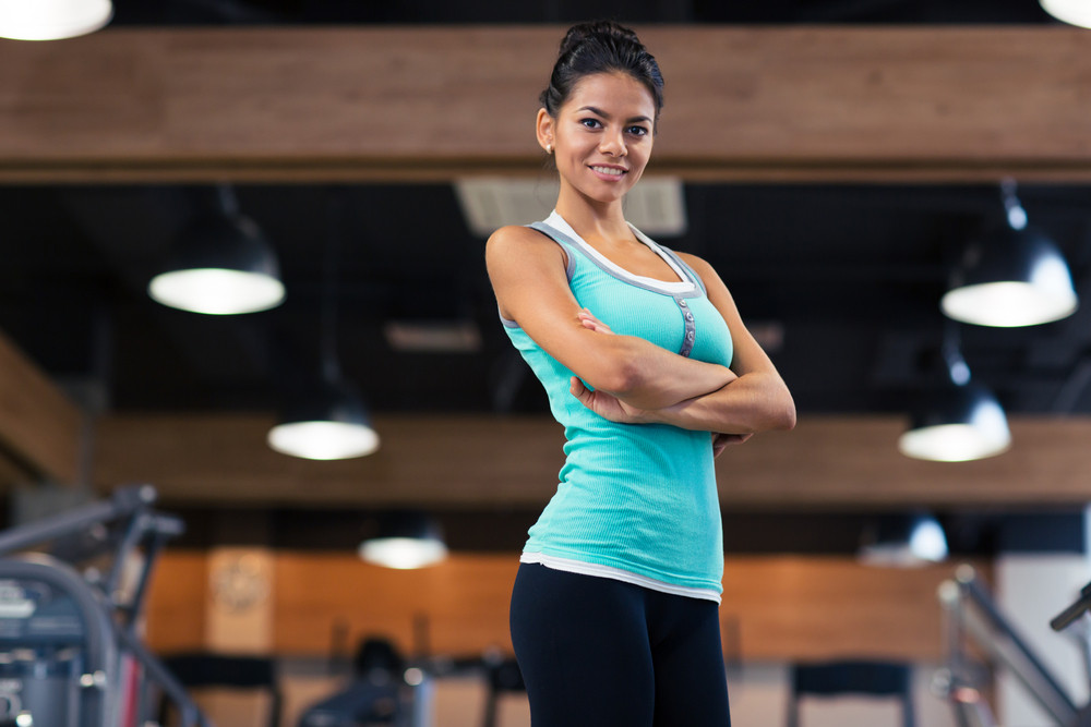 Sports woman standing with arms folded in gym