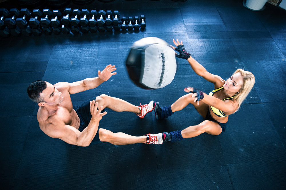 Muscular man and woman workout with fitball
