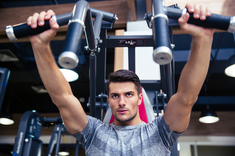 Man doing exercise on fitness machine in gym