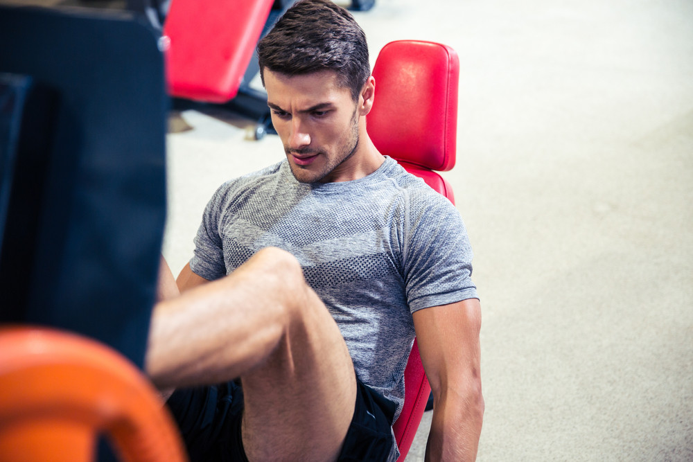 Man doing legs exercises on a fitness machine