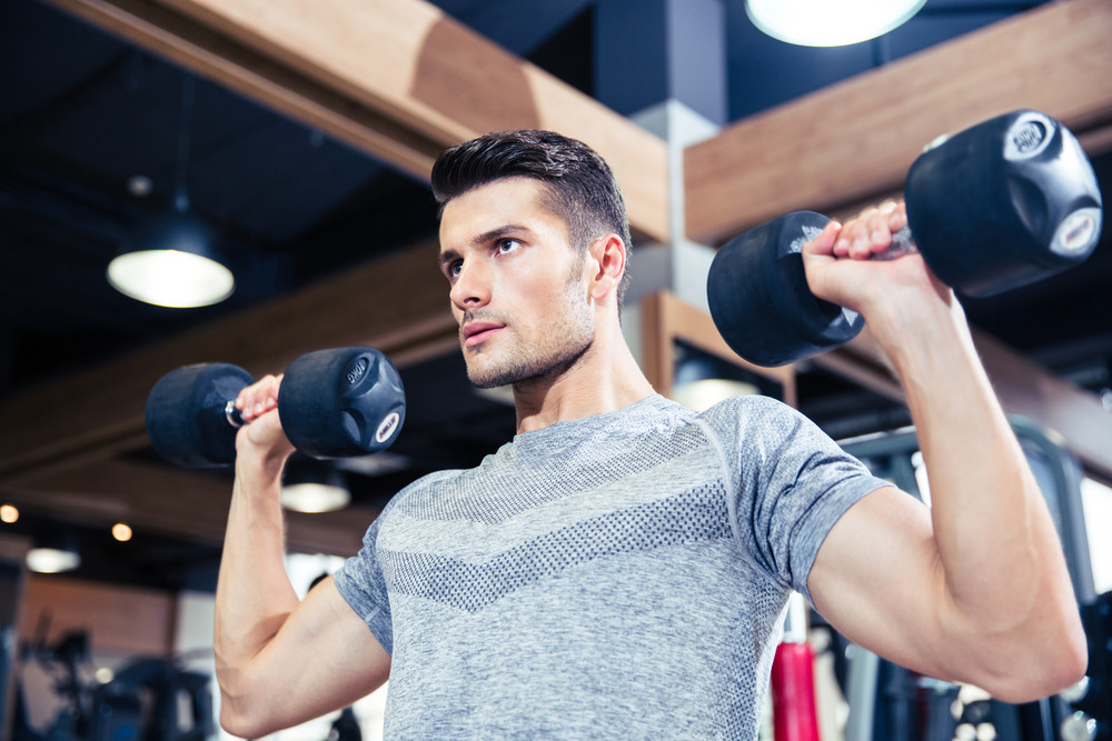 Man doing exercises with dumbbells at gym