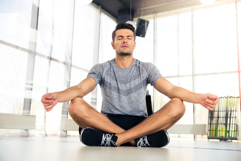 Man meditating in fitness gym