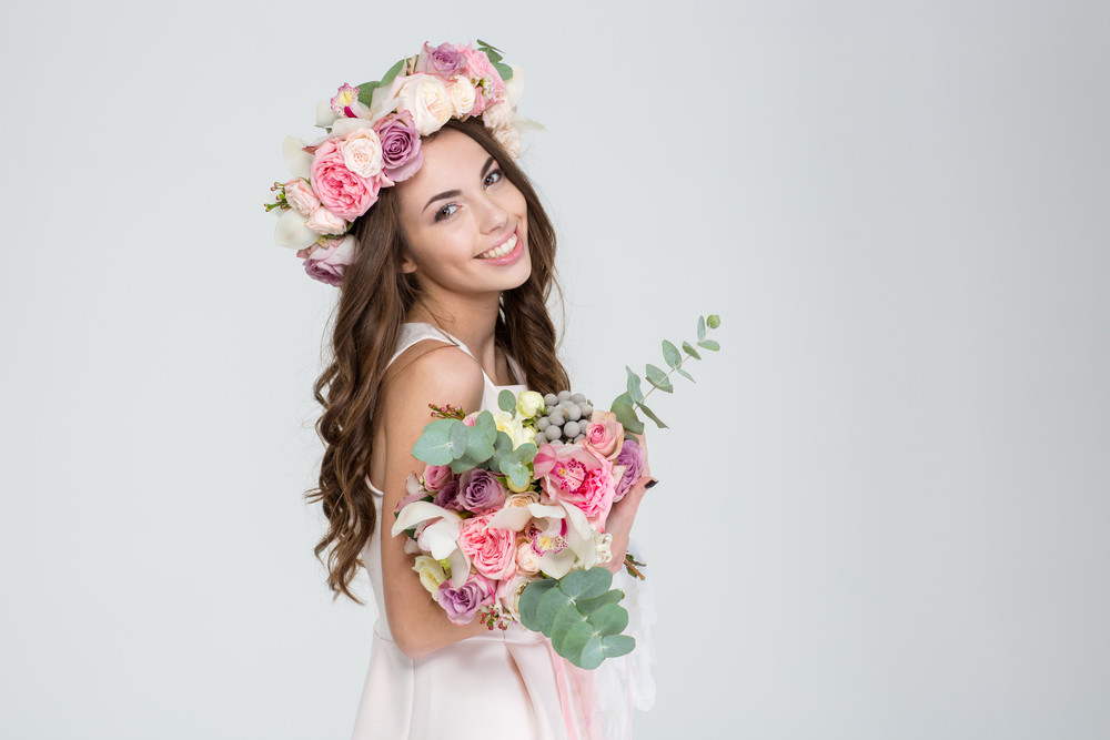 Beautiful happy bride in rose wreath holding bouquet of flowers