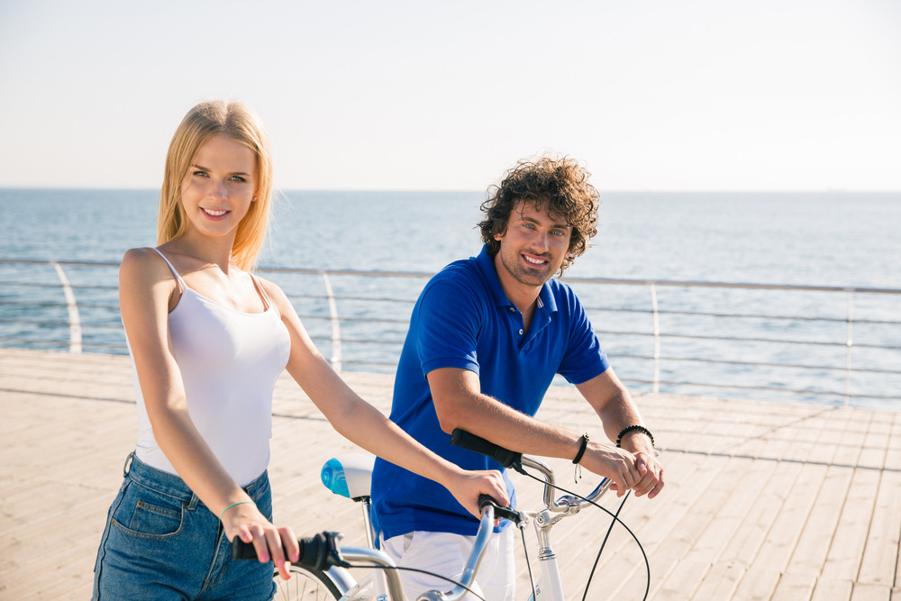 Man and woman walking with bicycle outdoors