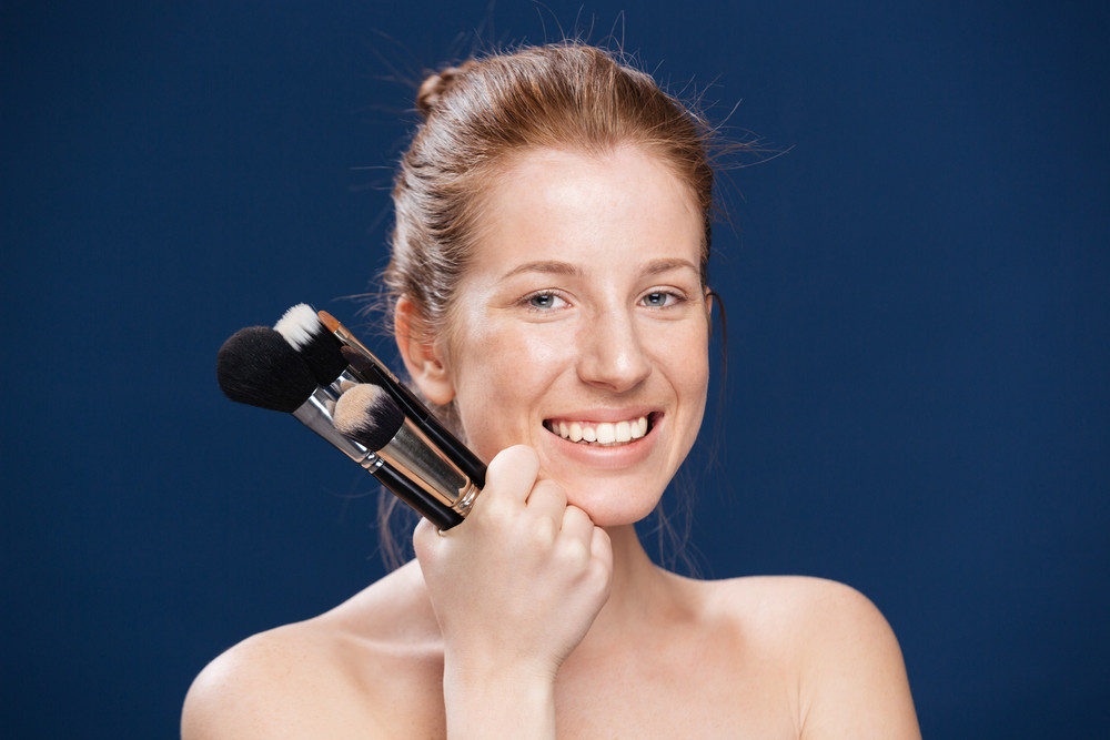 Smiling woman holding makeup brushes