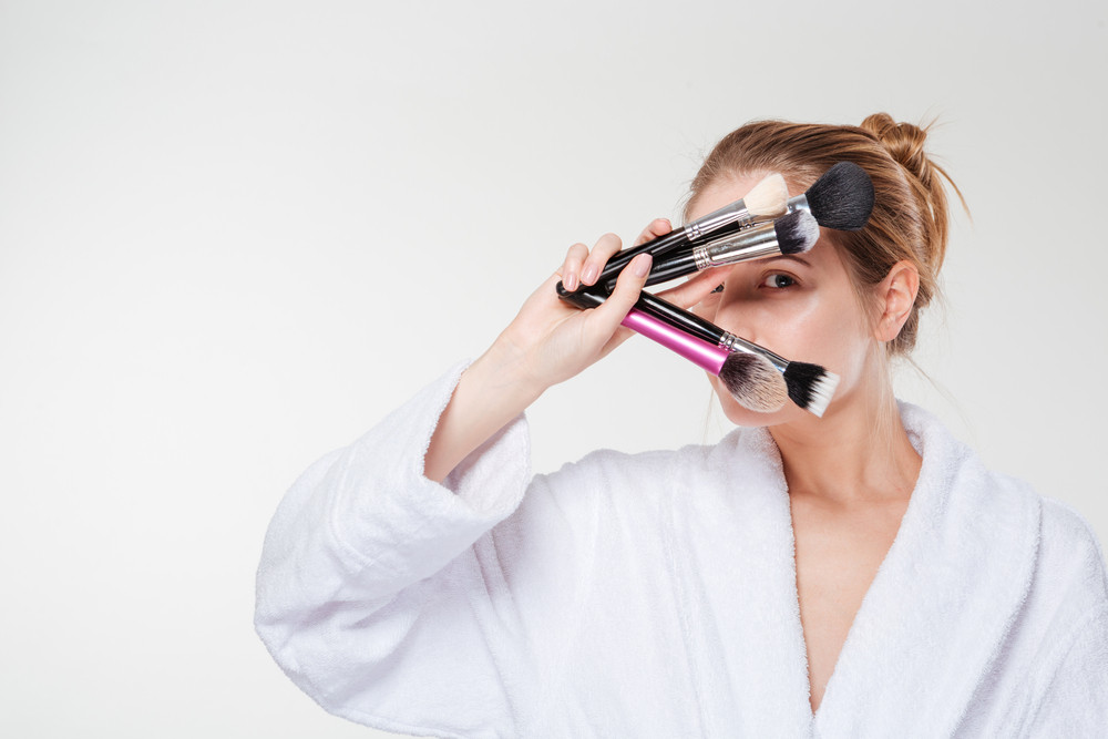 Woman in bathrobe holding makeup brushes