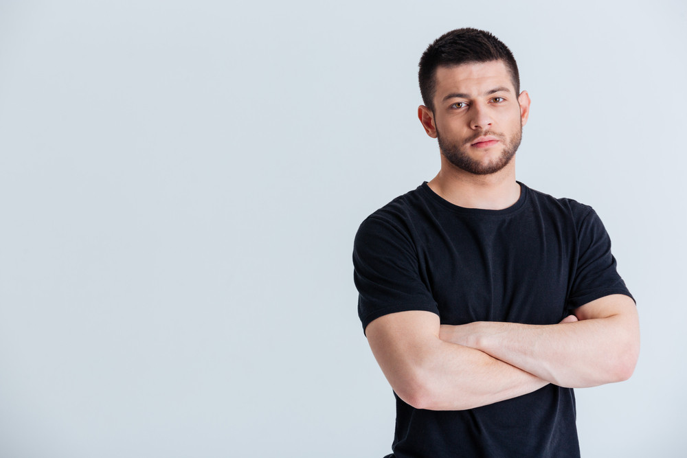Sports man standing with arms folded