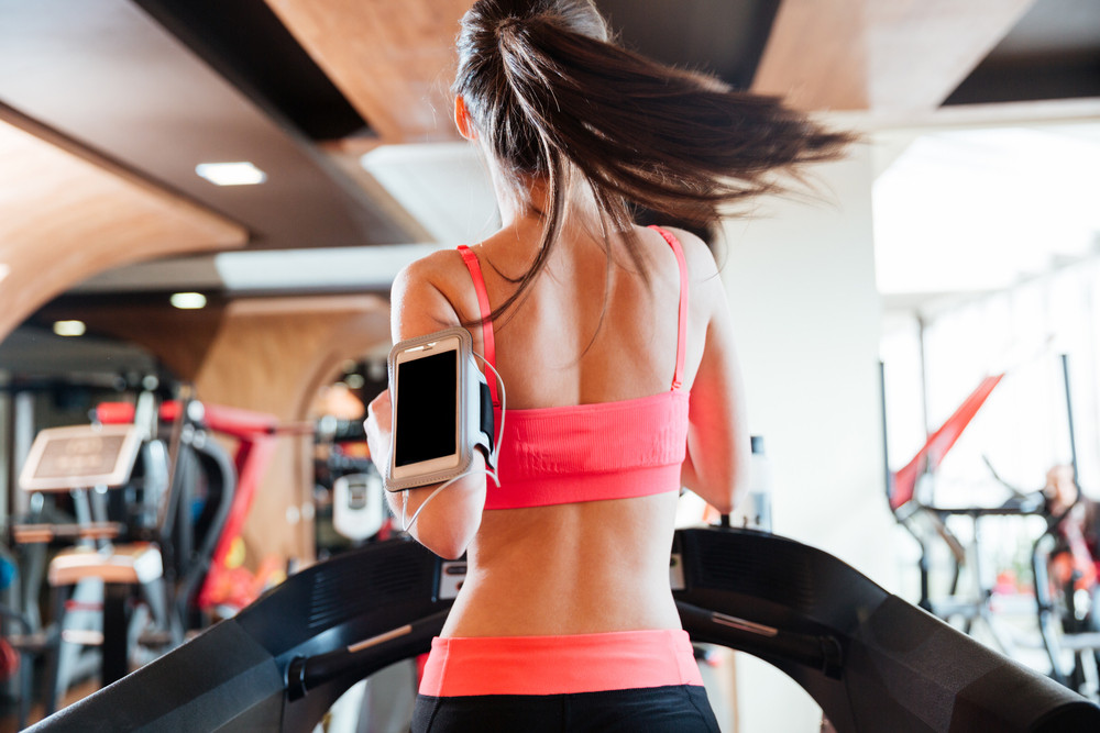 Woman athlete with balnk screen smartphone running on treadmill