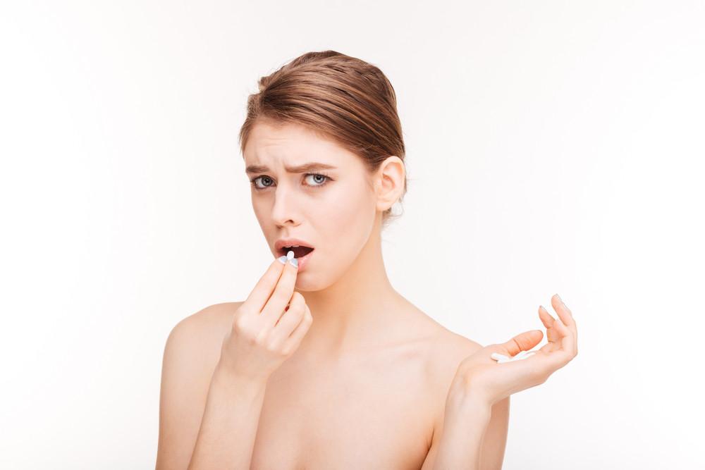 Sad woman holding pill