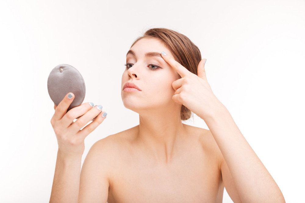 Woman with fresh skin holding mirror