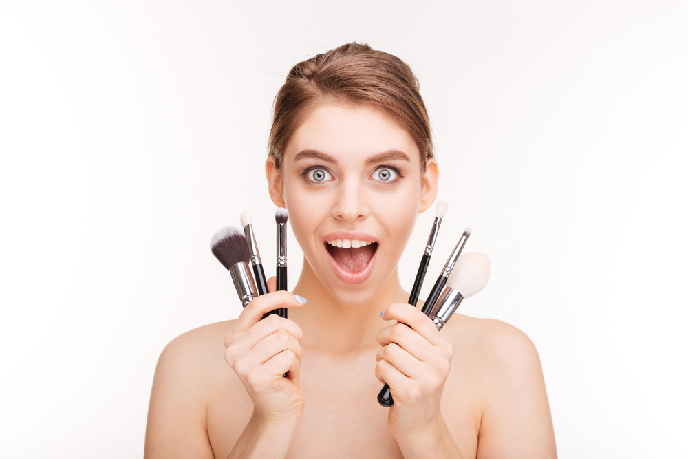 Beauty portrait of happy excited young woman with makeup brushes